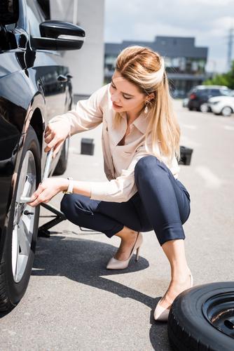 donna-d-affari-fissaggio-ruota-su-auto-rotto--concetto-di-assicurazione-auto